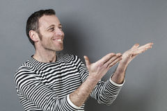 Ecstatic 40s man holding or presenting something Stock Image