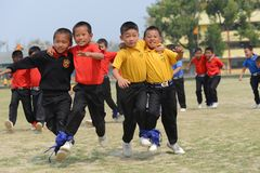 Free Ecstatic School Students Competing In Three Legged Race Stock Image - 127822191