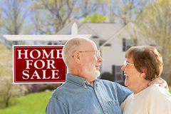 Ecstatic Senior Couple Front of For Sale Sign and House Stock Photography