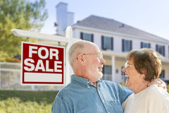 Ecstatic Senior Couple Front of For Sale Sign and House Stock Photo