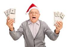 Ecstatic senior with Santa hat holding money Stock Photo