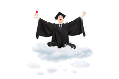 Ecstatic student holding diploma sitting on cloud and gesturing stock photography