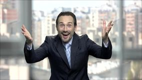 Ecstatic successful businessman raised hands in excitement. Lucky emotional executive rejoicing and celebrating victory with hand gesture. Personal successful stock video footage