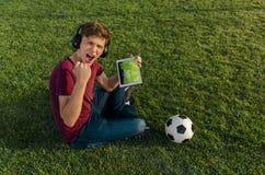 Ecstatic teen, soccer fan holding tablet stock images