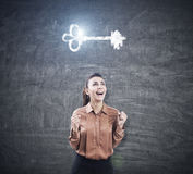 Ecstatic woman in brown and key sketch. Ecstatic woman in   standing with an open mouth and her hands in the air near a blackboard with a glowing key sketch Royalty Free Stock Photography