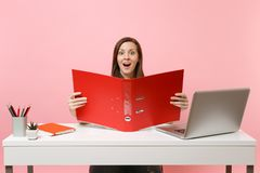 Ecstatic woman looking on red folder with paper documents, working on project while sitting at office with laptop royalty free stock image