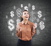 Ecstatic woman near a chalkboard with dollar signs Stock Photo