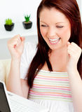 Ecstatic woman using her laptop sitting on a sofa Royalty Free Stock Image