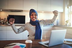 Ecstatic young Arabic woman celebrating her business success at royalty free stock image