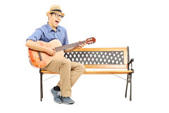Ecstatic young guitarist sitting on bench and singing Royalty Free Stock Photos
