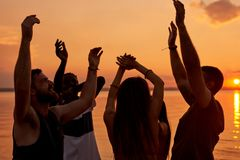 Ecstatic young students enjoying beach party at sunset royalty free stock photo