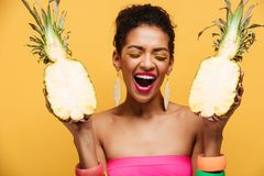 Ecstatic young woman with afro hairstyle and colorful makeup holding two halves of fresh appetizing pineapple isolated, over yell. Ecstatic young woman with afro royalty free stock images