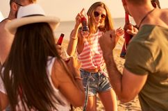 Ecstatic youth drinking alcohol and dancing on beach. Jolly carefree young friends drinking alcohol and standing around while dancing and having fun at beach royalty free stock photo