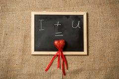 Ecuación del amor escrita en la pizarra con el corazón rojo Foto de archivo libre de regalías
