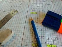 Ecuaciones de la matemáticas solucionadas en la página, con el lápiz, marcadores coloridos, er fotografía de archivo