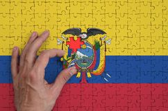 Ecuador flag is depicted on a puzzle, which the man`s hand completes to fold.  royalty free illustration