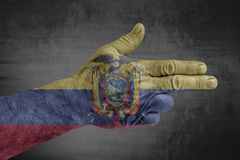 Ecuador flag painted on male hand like a gun. On concrete background royalty free stock photo