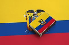 Ecuador flag is pictured on a matchbox that lies on a large flag.  royalty free stock photography