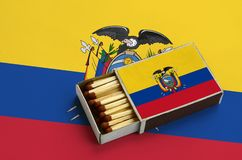 Ecuador flag is shown in an open matchbox, which is filled with matches and lies on a large flag.  royalty free stock image