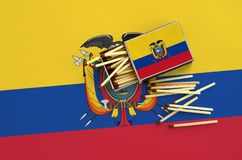 Ecuador flag is shown on an open matchbox, from which several matches fall and lies on a large flag.  stock images