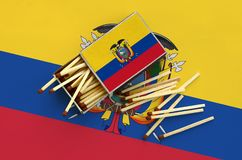 Ecuador flag is shown on an open matchbox, from which several matches fall and lies on a large flag.  royalty free stock images