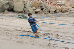 Ecuadorian fishermen child pulling in their nets royalty free stock images