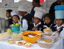 Ecuadorian-Kinder, die traditionelle Nahrung kochen Stockbild