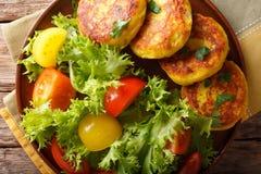 Ecuatoriaanse llapingachos van aardappelpannekoeken en vers saladeclose-up Stock Afbeelding
