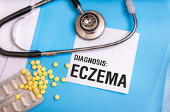 Eczema word written on medical blue folder with patient files. Pills and stethoscope on background stock photo