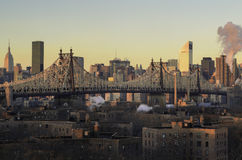 Ed Koch Queensboro Bridge. The sun is rising. The forth ground are Jacob A. Riis Neighborhood Settlement Houses. In the middle is the Ed Koch Queensboro Bridge Royalty Free Stock Image
