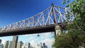 Ed Koch Queensboro Bridge Low Angle Establishing Shot. A low angle daytime establishing shot of the Ed Koch Queensboro Bridge with the Roosevelt Island Tram stock video footage