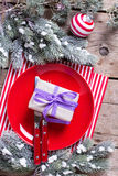 Ed  plate, knife and fork, napkin and  wrapped present on rustic Stock Photos