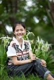 Edad adolescente que se sienta en el parque Imagen de archivo
