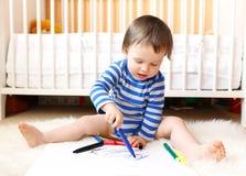 Edad del bebé de 18 meses de pinturas con las plumas Fotografía de archivo