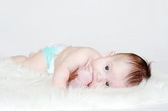 Edad del bebé de 4 meses que mienten en la tela escocesa de la piel Foto de archivo libre de regalías