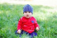 Edad del bebé de 11 meses que se sientan en hierba Foto de archivo