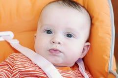 Edad divertida del bebé de 5 meses que se sientan en el highchair Foto de archivo