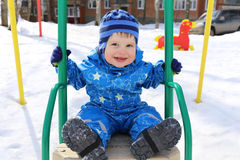 Edad feliz del bebé de 18 meses en la oscilación en invierno Foto de archivo libre de regalías