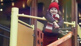Edad sonriente feliz 3-4 de la muchacha en la ropa caliente que se coloca en una diapositiva en el patio colorido brillante almacen de video