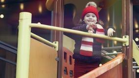 Edad sonriente feliz 3-4 de la muchacha en la ropa caliente que se coloca en una diapositiva en el patio colorido brillante A cám metrajes