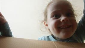 Edad sonriente feliz de la niña 3-4 años que desempaquetan y que abren la caja del cartón, y mirando dentro con sorpresa Ella es almacen de video