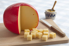 Edam cheese and cubes. On a cutting board stock photography