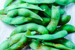 Edamame beans in artistic colorful processing. Edamame beans in salt and spices. Boiled immature soybeans in pods on a wooden cutting board with blurred royalty free stock photos