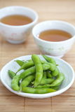 Edamame nibbles, boiled green soy beans Stock Photos