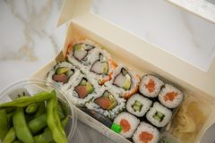 Edamame, salmon, surimi, cucumber and avocado Maki and inside out California sushi with soy sauce, pickled ginger, wasabi and soy royalty free stock images