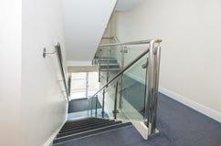 Edelstahlhandlauf- und -glasplatten auf Treppenhaus Stockfotos