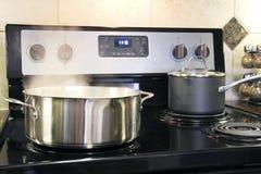 Edelstahltöpfe, die auf Küchenofen kochen Stockfoto