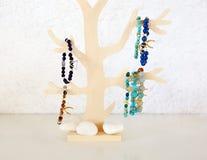 Edelsteinschmuckanzeige verziert auf einem hölzernen Baum Lizenzfreie Stockbilder