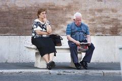 Ederly夫妇坐长凳 免版税库存照片