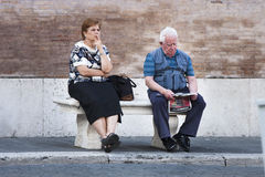 Ederly couple sitting on a bench. An elderly couple is sitting on a bench. He is reading a newspaper. But she is thinking with her hand over her mouth. Location Royalty Free Stock Photo
